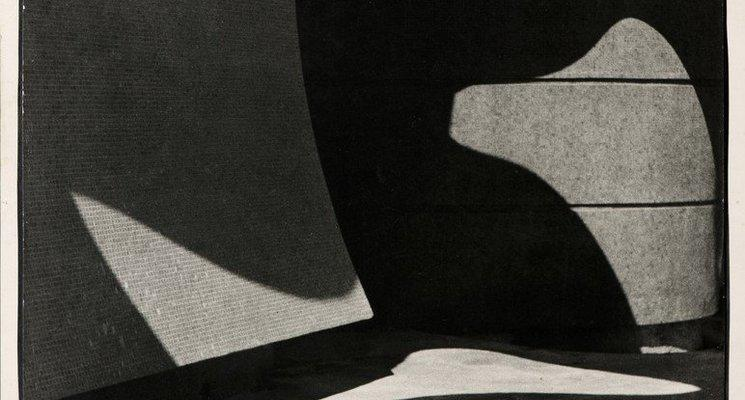 Imagem em preto e branco do artista José Yalenti. A imagem mostra um lugar vazio sob luzes e sombras, formadas a partir de aberturas no teto e que revelam formas abstratas nas paredes e no chão.